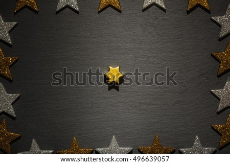 Golden star candle on slate background with frame of golden and silver stars, Christmas decoration.
