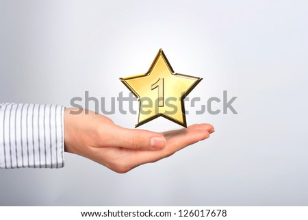 Golden star in hands. Number one. - stock photo