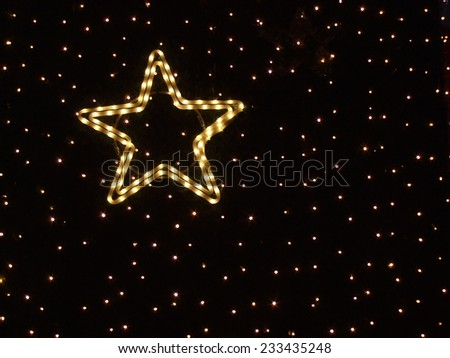 Golden star shaped light rope and many little lights forming artificial starry sky - stock photo