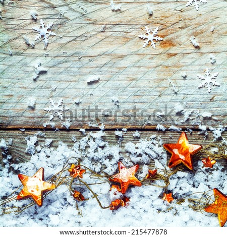 Golden stars with snow and falling snowflake decorations in a rustic Xmas background with copyspace for your Christmas greeting, square format - stock photo