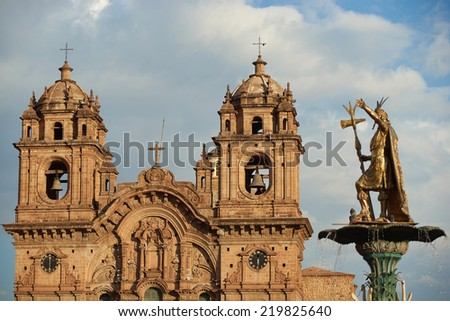 Golden statue of an Inca on top of the fountain in the centre of the Plaza de Armas in Cusco, Peru. In the background is the historic Iglesia de la Compania, which dates back to 1571. - stock photo