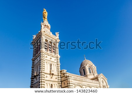 Golden Statue of the Madonna Holding the little Jesus on the top of Notre-Dame de la Garde in Marseilles, France - stock photo