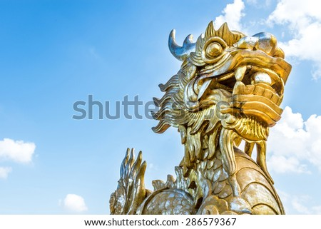 Golden stone dragon statue in Vietnam with face close-up on blue sky background. Leftside view. Symbol of vietnamese mythology and folklore. Religion, culture and art of Asia.