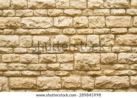 Golden stone rock wall texture background. - stock photo