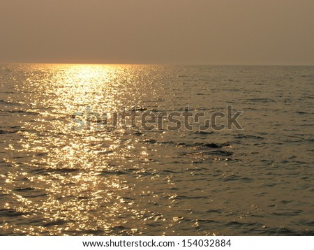 Golden sun reflection on sea background wallpaper - stock photo