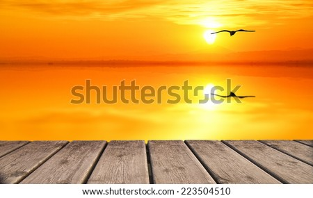 golden sun set from wooden jetty - stock photo