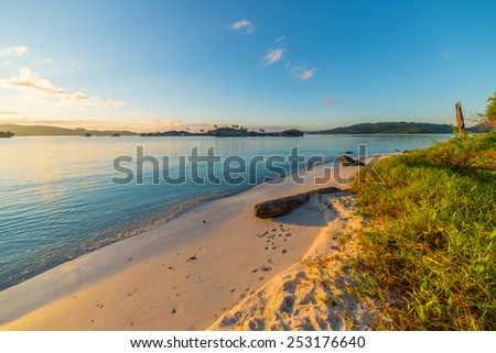 Golden sunrise on desert white sandy beach. Tourist resort in the remote Togean (or Togian) Islands, Central Sulawesi, Indonesia, upgrowing travel destination for young hipsters. - stock photo