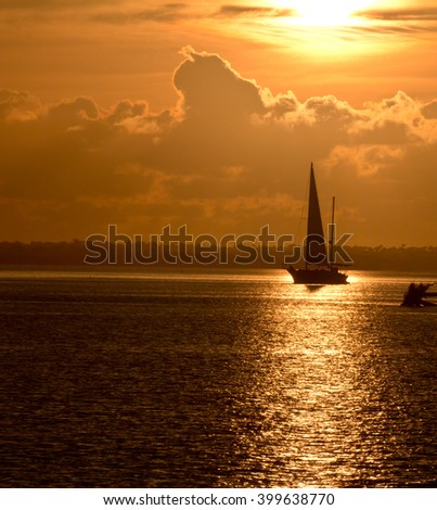 Golden sunrise with a sailboat in the reflected rays