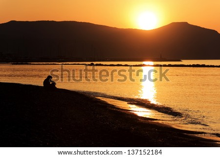 Golden sunset as seen from Latchi beach over the hills of Akamas peninsula, Cyprus - stock photo