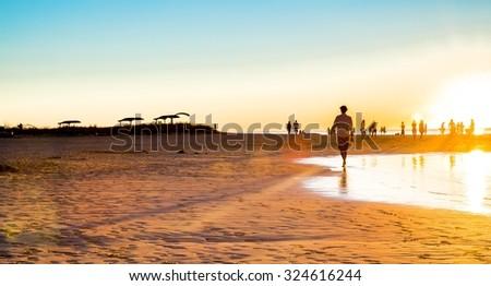 Golden sunset beach Australia silhouette people man boat summer - stock photo