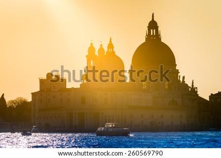 Golden sunset behind the Santa Maria della Salute church in Venice, Italy - stock photo