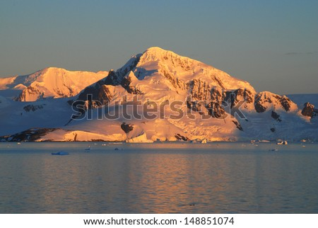 Golden sunset on icy mountains - stock photo