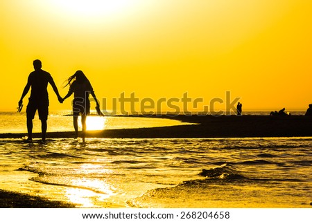 Golden sunset over the sea and the silhouettes of the lovers in the summer evening - stock photo