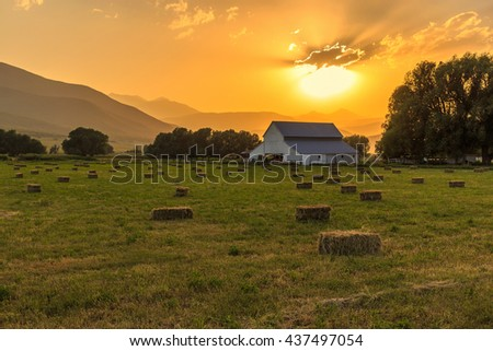 Golden sunset with a white barn in rural Utah, USA. - stock photo