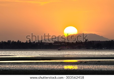 Golden Sunset with half of the sun behind the hill - stock photo