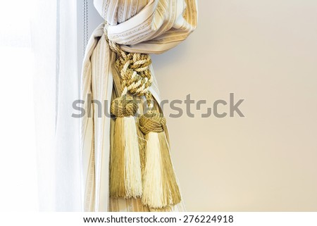 Golden tassel on the drapery - stock photo