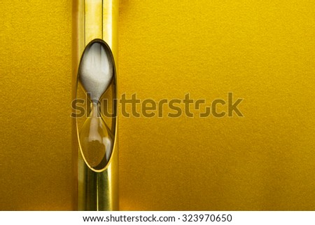 Golden time, gold hour glass in front of gold wall. - stock photo