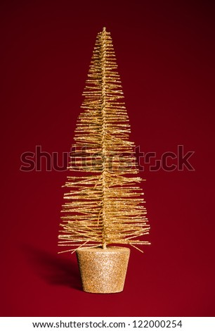 golden toy christmas tree on red
