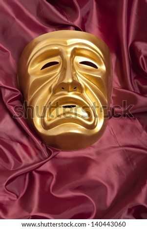 Golden tragedy theatrical mask on satin background - stock photo