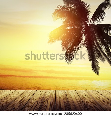Golden tropical banner background. Empty wooden table and sunset over the ocean. Coconut palm silhouette. - stock photo