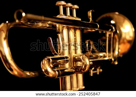 Golden trumpet on black background as seen from behind and low with the first keys in focus.