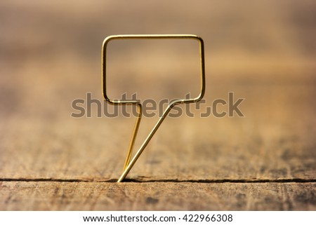 Golden tweet or remark. Blank speech bubble made of gold wire on rustic or grunge wood ready for inserting text. Shallow depth of field. - stock photo