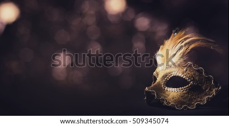 Golden venetian ball mask in front of the night bokeh lights. Masquerade party or holiday event celebration concept.