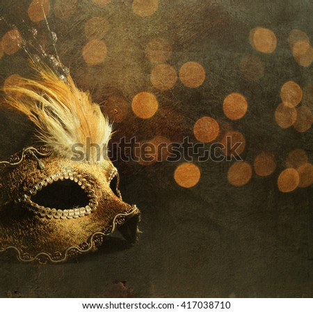 Golden venetian mask over shiny bokeh background with golden texture - stock photo