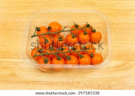 Golden vine tomatoes in a plastic carton on a wooden board - stock photo