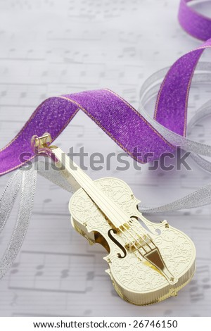 Golden violin with ribbons on music note background - stock photo