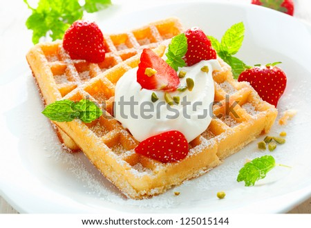 Golden waffle topped with fresh sliced strawberries and cream and sprinkled with sugar for a delicious dessert - stock photo