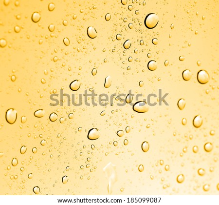 golden water drops on glass