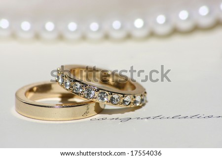 "golden wedding bands sitting on white card with ""congratulations"" on it"