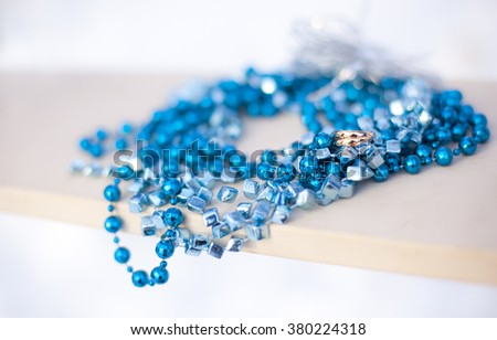 Golden wedding rings and blue garland on swing