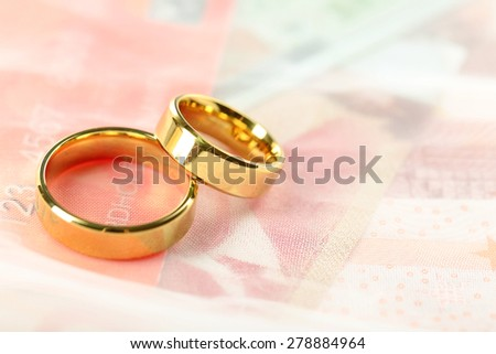 Golden wedding rings and credit card, close up. Marriage of convenience concept - stock photo