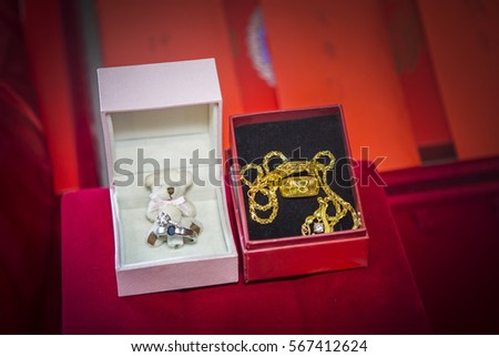 Golden wedding rings and necklace with diamonds on red background. Symbol of love and marriage.