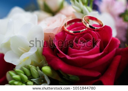 Golden wedding rings on a rose flower in a bouquet