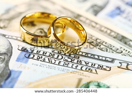Golden wedding rings on banknotes background. Marriage of convenience - stock photo