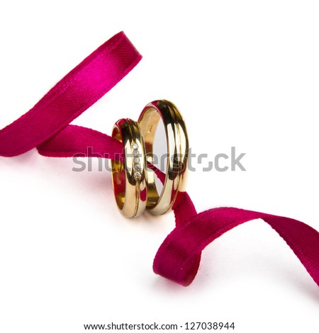 Golden wedding rings over  ribbon isolated - stock photo