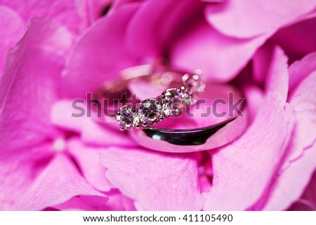 Golden wedding rings with diamonds on the tender pink flower