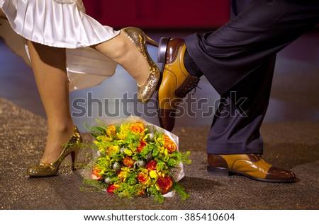 Golden wedding shoes of bride, brown wedding shoes of groom and colorful wedding bouquet  - stock photo