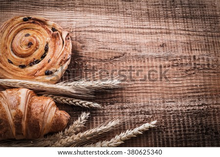 Golden wheat ears bun with raisins home-cooked croissant on oaken wooden board food and drink concept. - stock photo