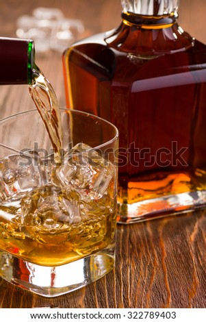 Golden Whiskey Being Poured with Fine Crystal Whiskey Bottle