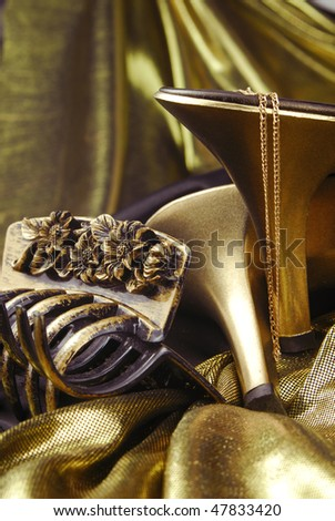 golden womans shoes and accessories  on golden fabric - stock photo
