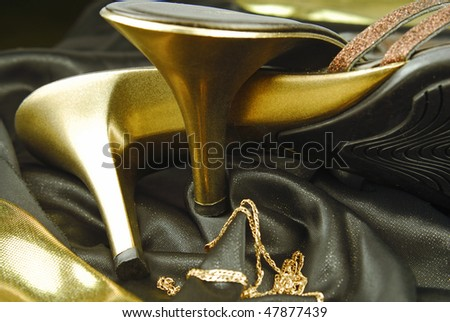 golden womans shoes and golden jewellery - stock photo