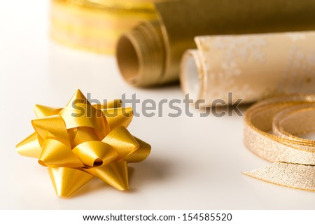 Golden wrapping paper and bow for christmas present decoration - stock photo
