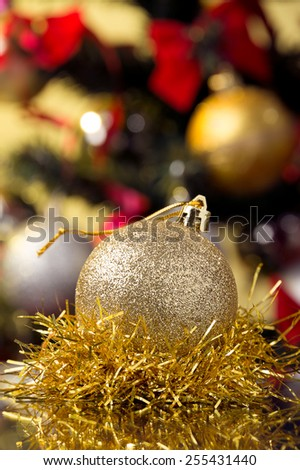 golden xmas ball,matte surface placed on gold tinsel, xmas tree for background  - stock photo