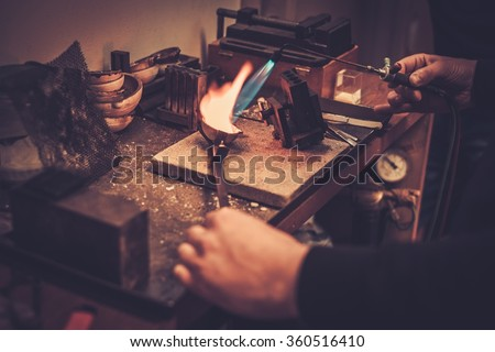 Goldsmith melting gold to liquid state in crucible with gasoline burner. - stock photo