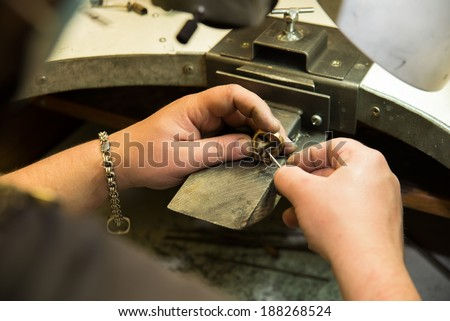 Goldsmith polishing gold ring with  hands - stock photo