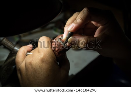 Goldsmith setting diamond on 18 karat white gold earring  - stock photo